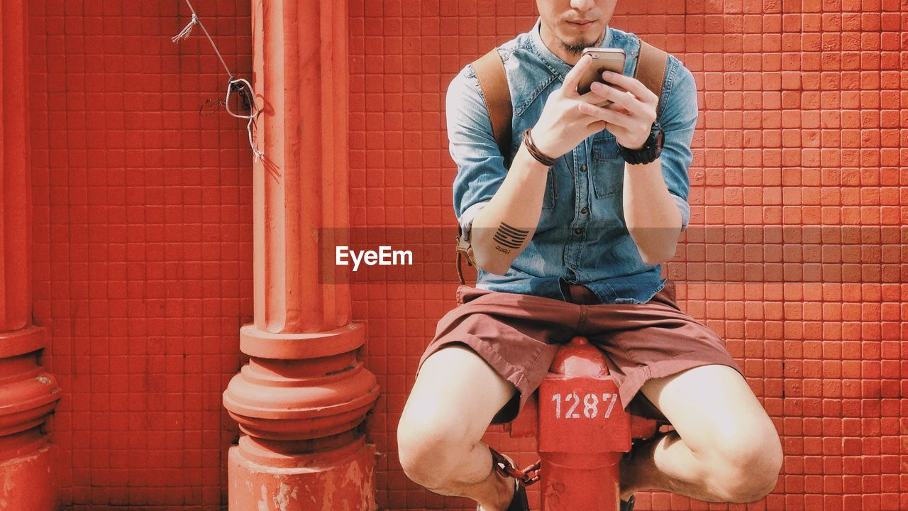 Young Man Sitting On Fire Hydrant And Using Smart Phone