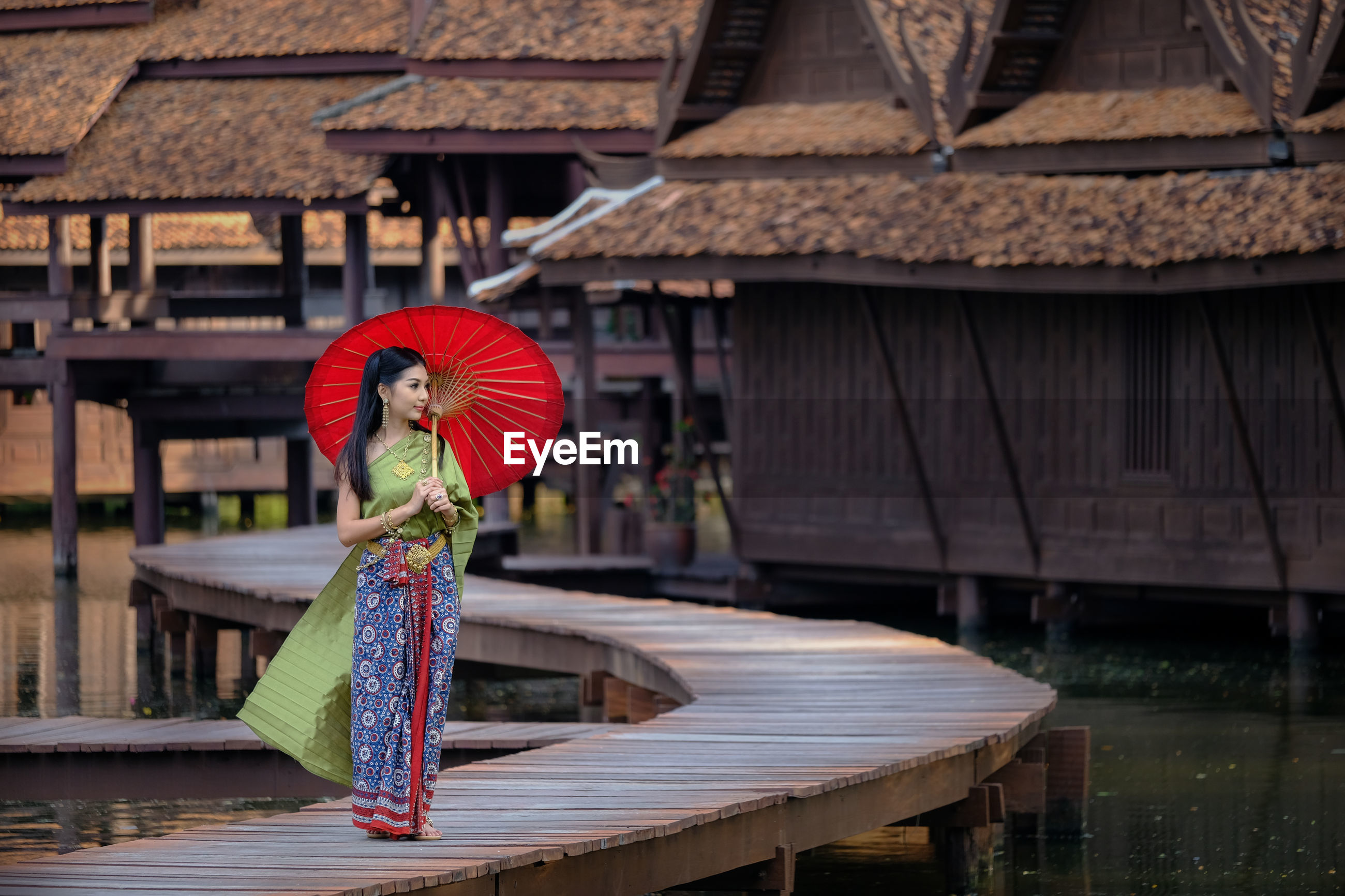 Beautiful young woman standing with umbrella on pier against stilt houses