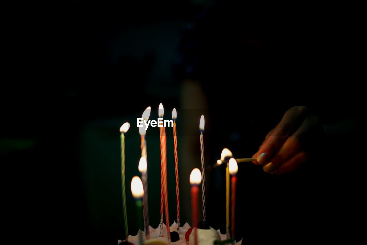 flame, candle, burning, heat - temperature, religion, human hand, glowing, spirituality, illuminated, human body part, celebration, matchstick, close-up, focus on foreground, real people, place of worship, birthday candles, indoors, one person, diya - oil lamp, diwali, night, hope, people