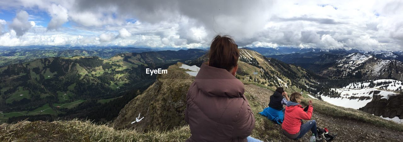 mountain, leisure activity, scenics - nature, cloud - sky, rear view, beauty in nature, women, lifestyles, mountain range, real people, sky, adult, non-urban scene, nature, landscape, hiking, day, people, adventure, environment, outdoors, looking at view, warm clothing