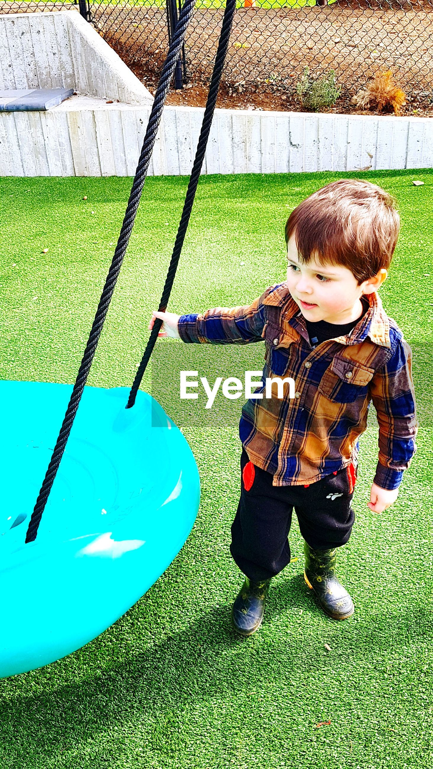 Full length of cute boy standing by swing in playground