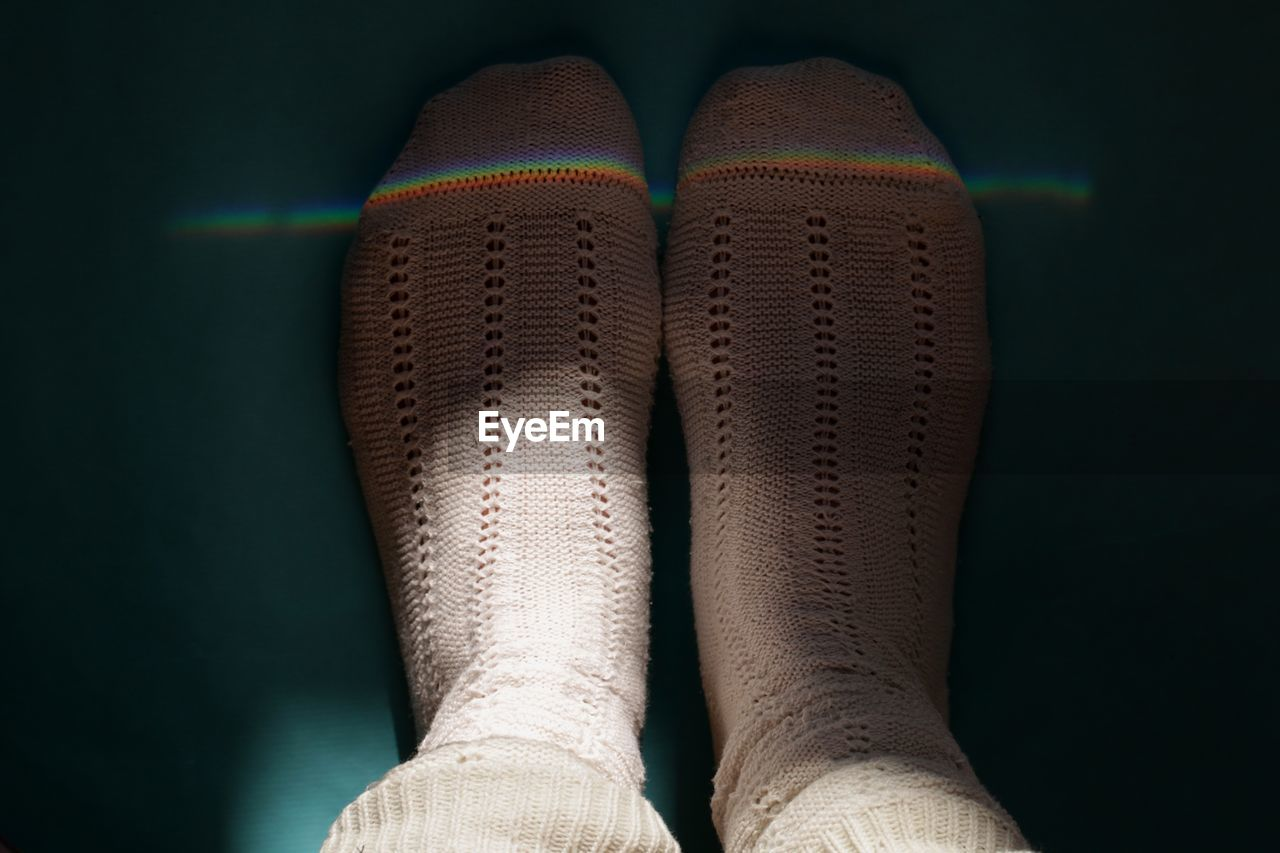 Low section of person wearing socks standing on floor