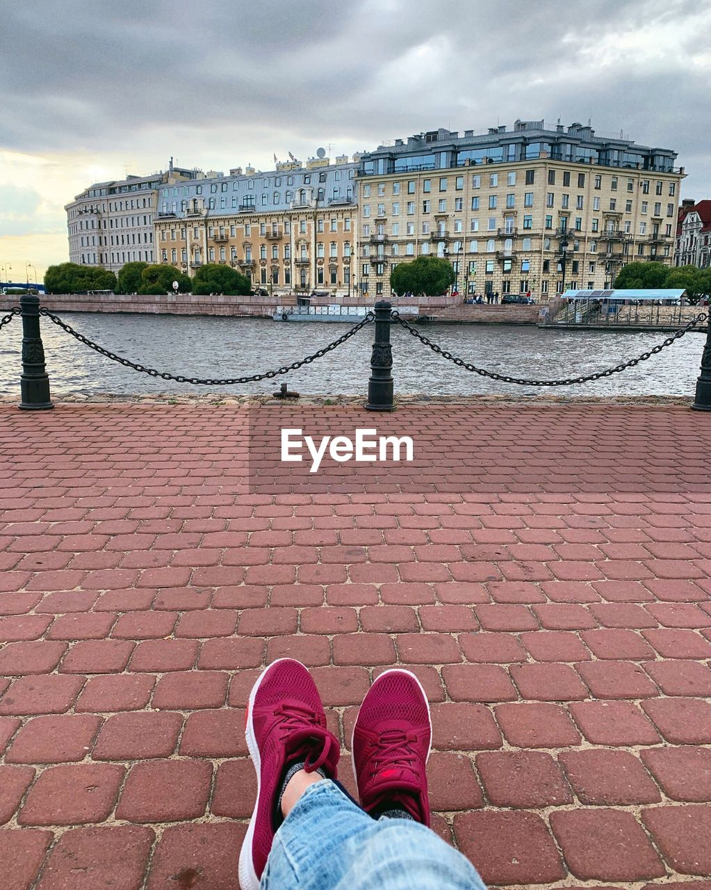 architecture, real people, low section, human leg, human body part, city, personal perspective, built structure, one person, shoe, water, body part, lifestyles, building exterior, sky, standing, cloud - sky, river, outdoors, jeans, human foot, human limb