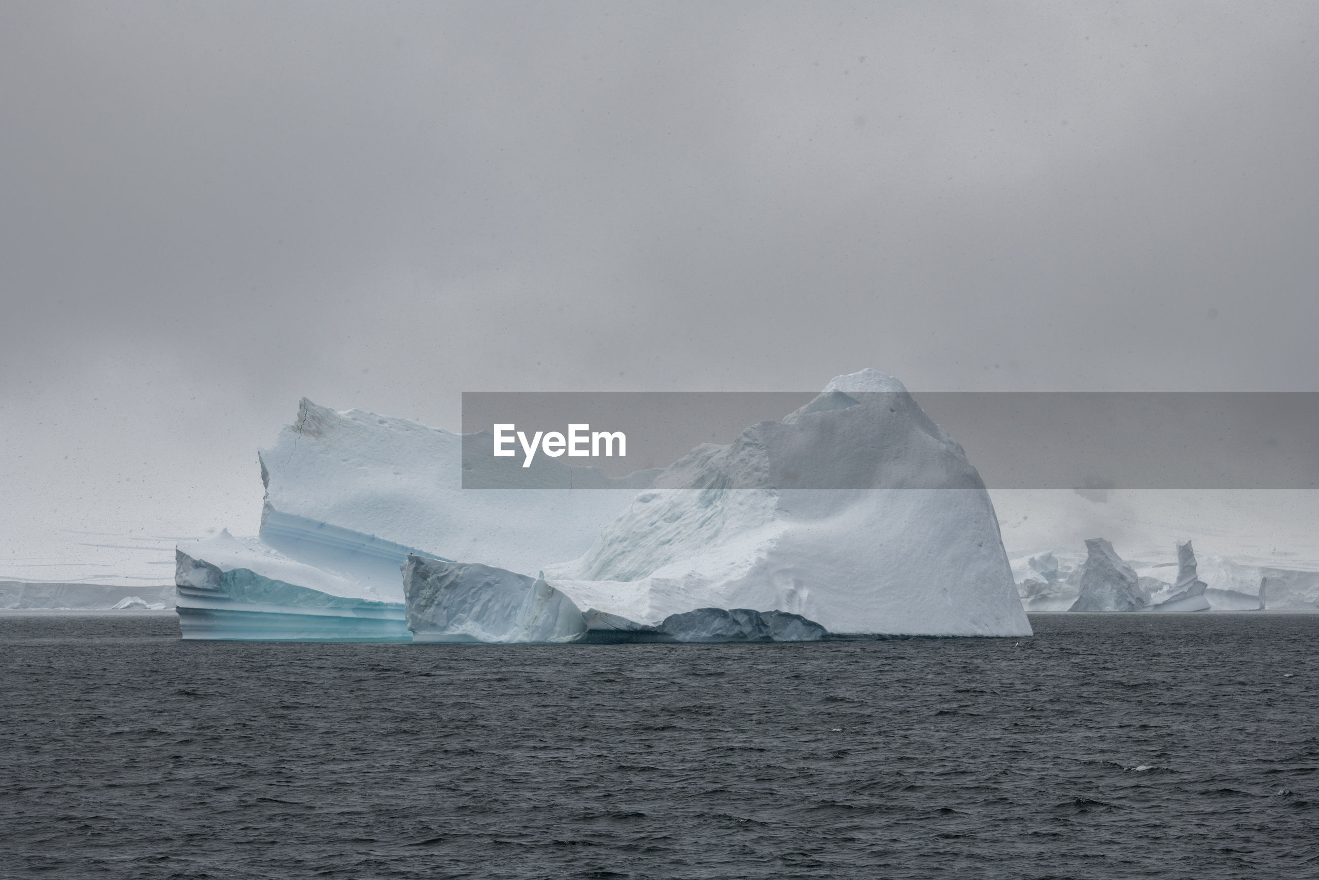 Scenic view of glacier in sea against sky