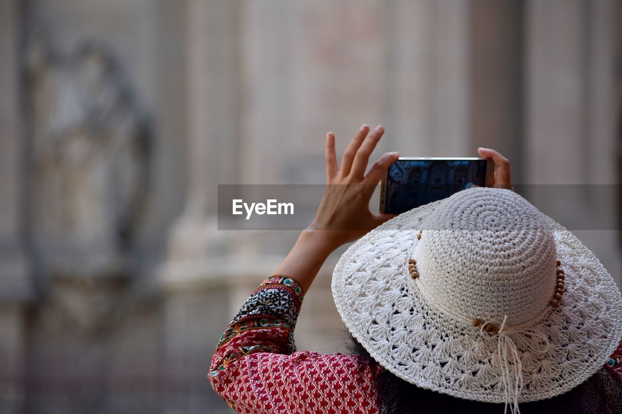 hat, one person, clothing, wireless technology, focus on foreground, communication, adult, photography themes, women, smart phone, real people, technology, photographing, mobile phone, day, leisure activity, holding, portable information device, lifestyles, hand, warm clothing