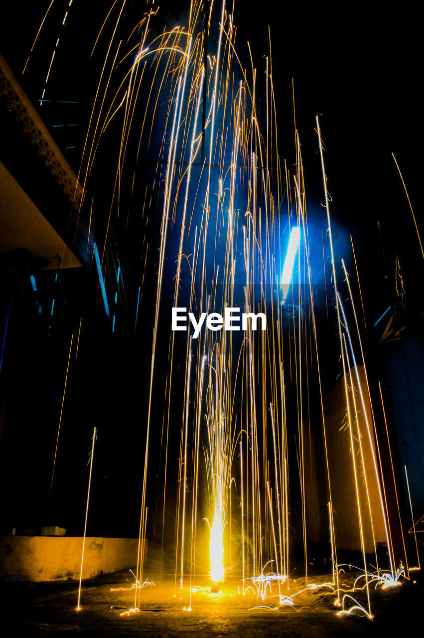 illuminated, night, long exposure, motion, glowing, blurred motion, no people, light trail, sparks, burning, architecture, nature, sky, low angle view, fire, lighting equipment, built structure, outdoors, fire - natural phenomenon, light, firework, firework - man made object, wire wool