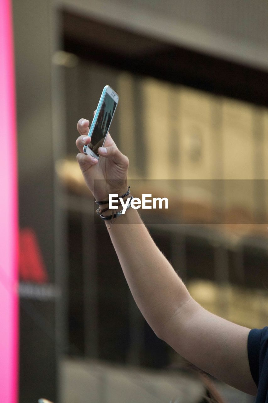 human hand, focus on foreground, wireless technology, smart phone, portable information device, mobile phone, connection, communication, human body part, technology, real people, holding, close-up, lifestyles, one person, day, outdoors, women, people