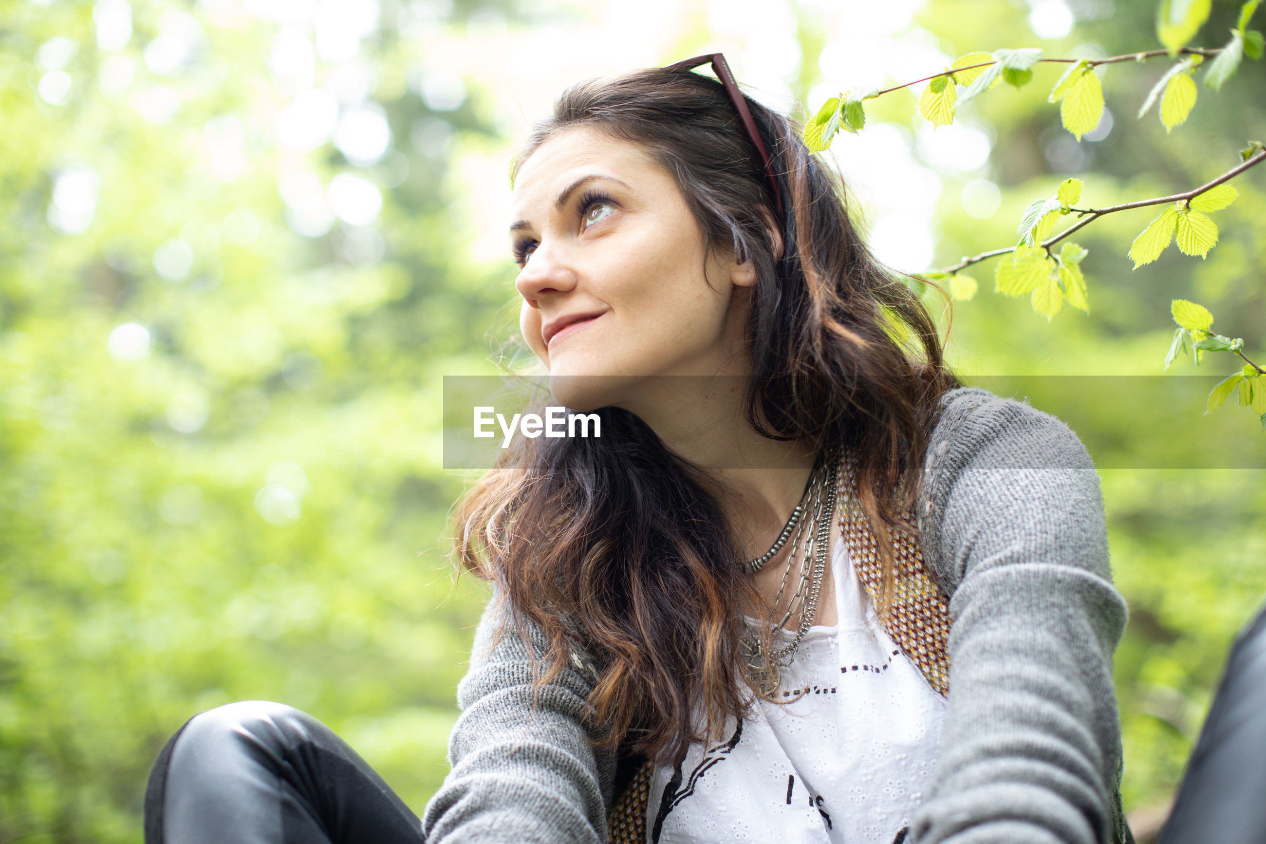 Low angle view of smiling woman sitting in forest