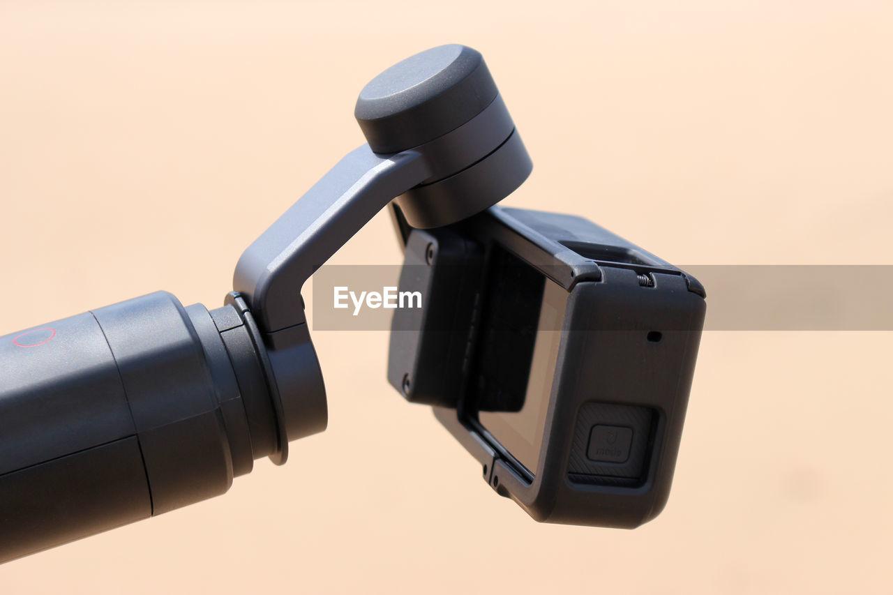 Close-up of digital video camera against beige background
