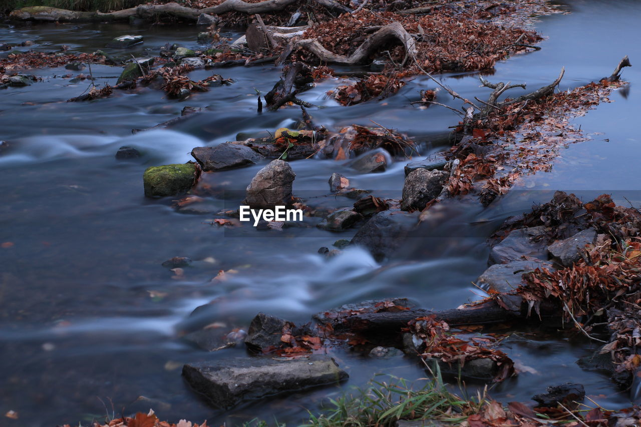 HIGH ANGLE VIEW OF ROCKS IN WATER BY LAKE
