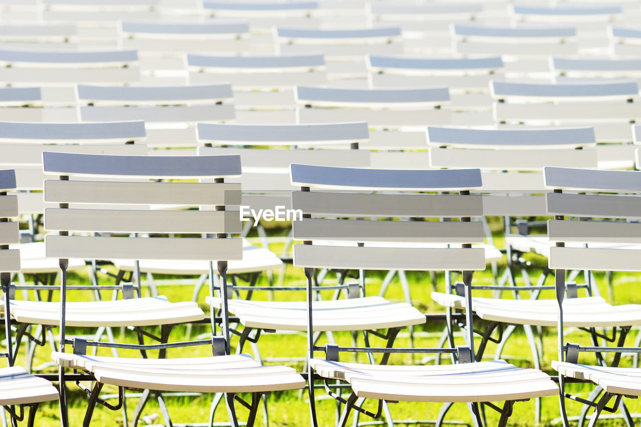 seat, chair, absence, in a row, empty, no people, large group of objects, repetition, arrangement, table, side by side, white color, furniture, order, day, full frame, sunlight, abundance, outdoors, high angle view