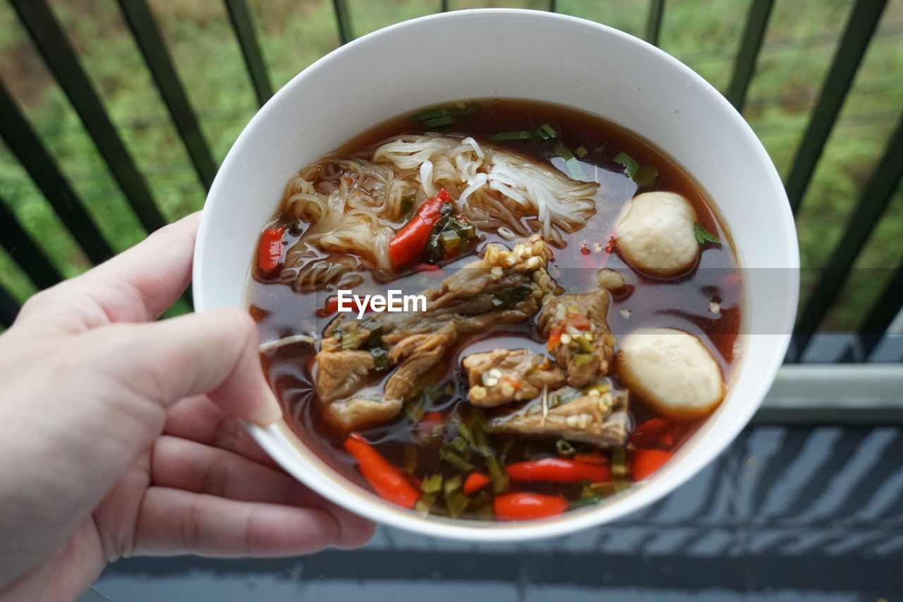 High angle view of hand holding soup in bowl