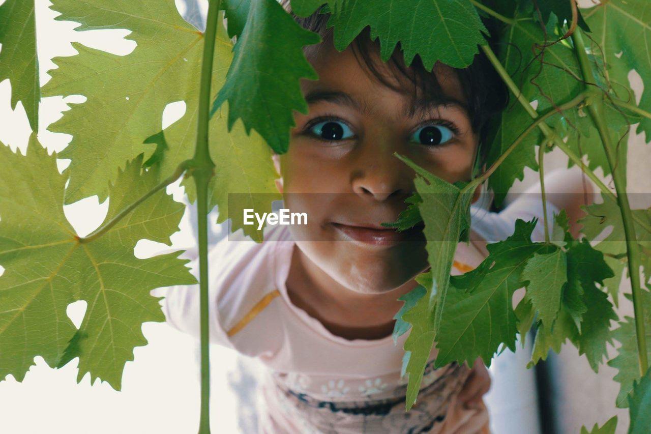Portrait Of Girl Looking Through Plants