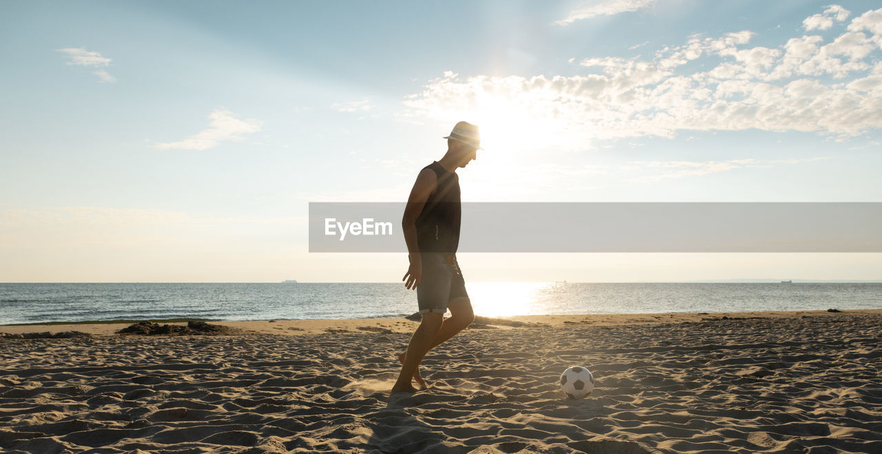 sky, sea, water, land, beach, horizon over water, one person, horizon, beauty in nature, real people, cloud - sky, sunlight, nature, scenics - nature, lifestyles, leisure activity, full length, sand, standing