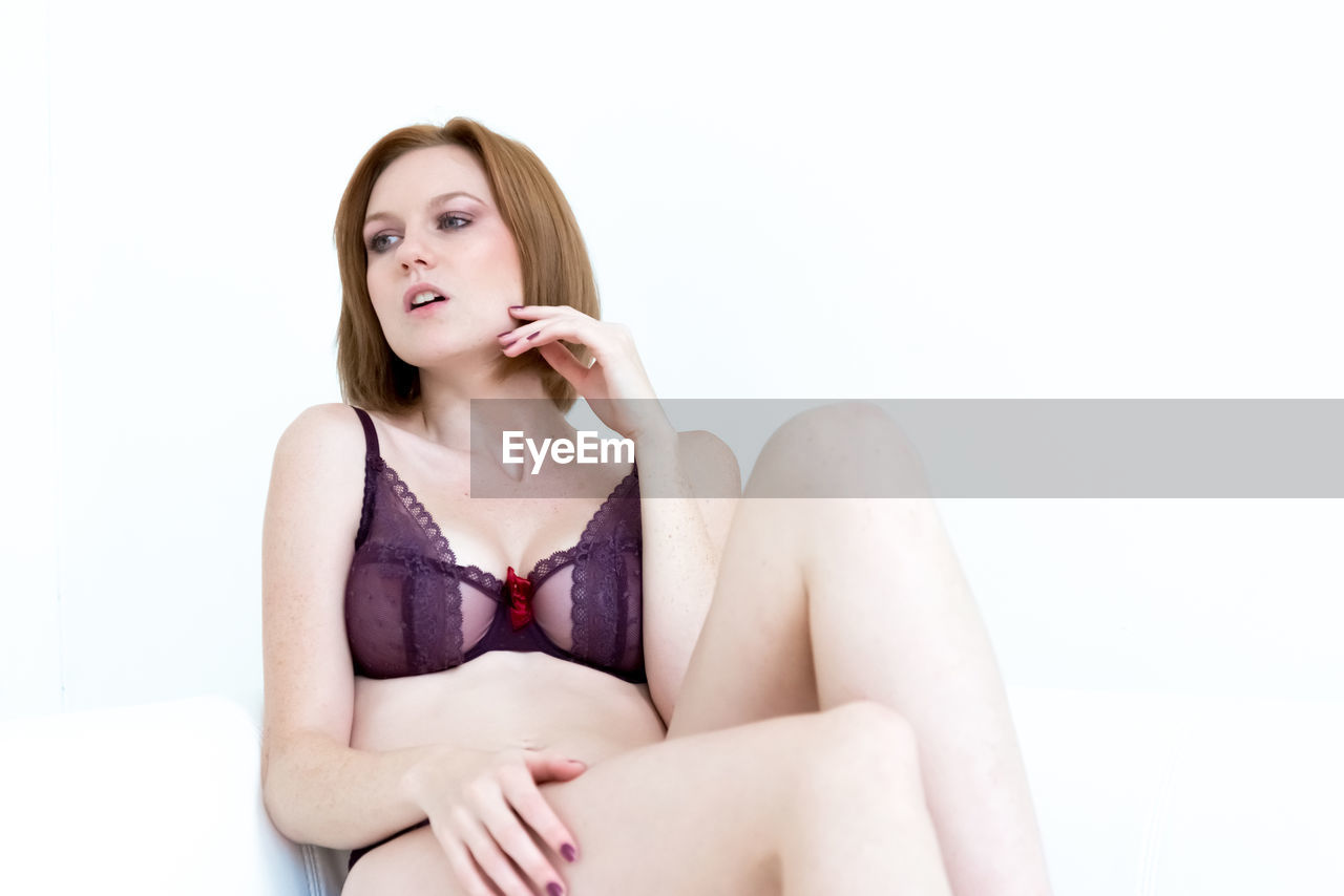 Young woman wearing lingerie while sitting against white background