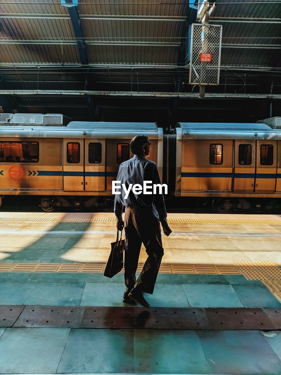 public transportation, real people, transportation, mode of transportation, railroad station platform, rail transportation, railroad station, men, train, train - vehicle, one person, lifestyles, casual clothing, full length, rear view, leisure activity, standing, travel, architecture, track, waiting, platform