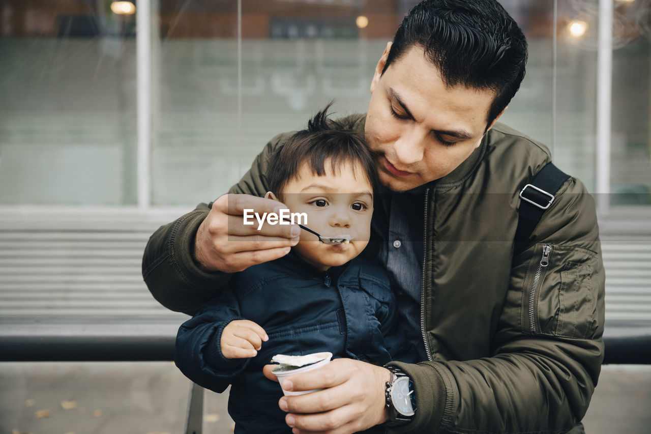 FATHER AND SON HOLDING CAMERA ON MAN