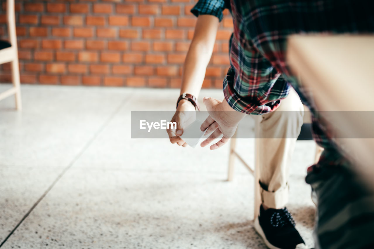 low section, human leg, human body part, real people, one person, women, body part, lifestyles, shoe, selective focus, adult, walking, casual clothing, day, leisure activity, wall, standing, motion, street, human limb, brick, shorts, tiled floor, human foot