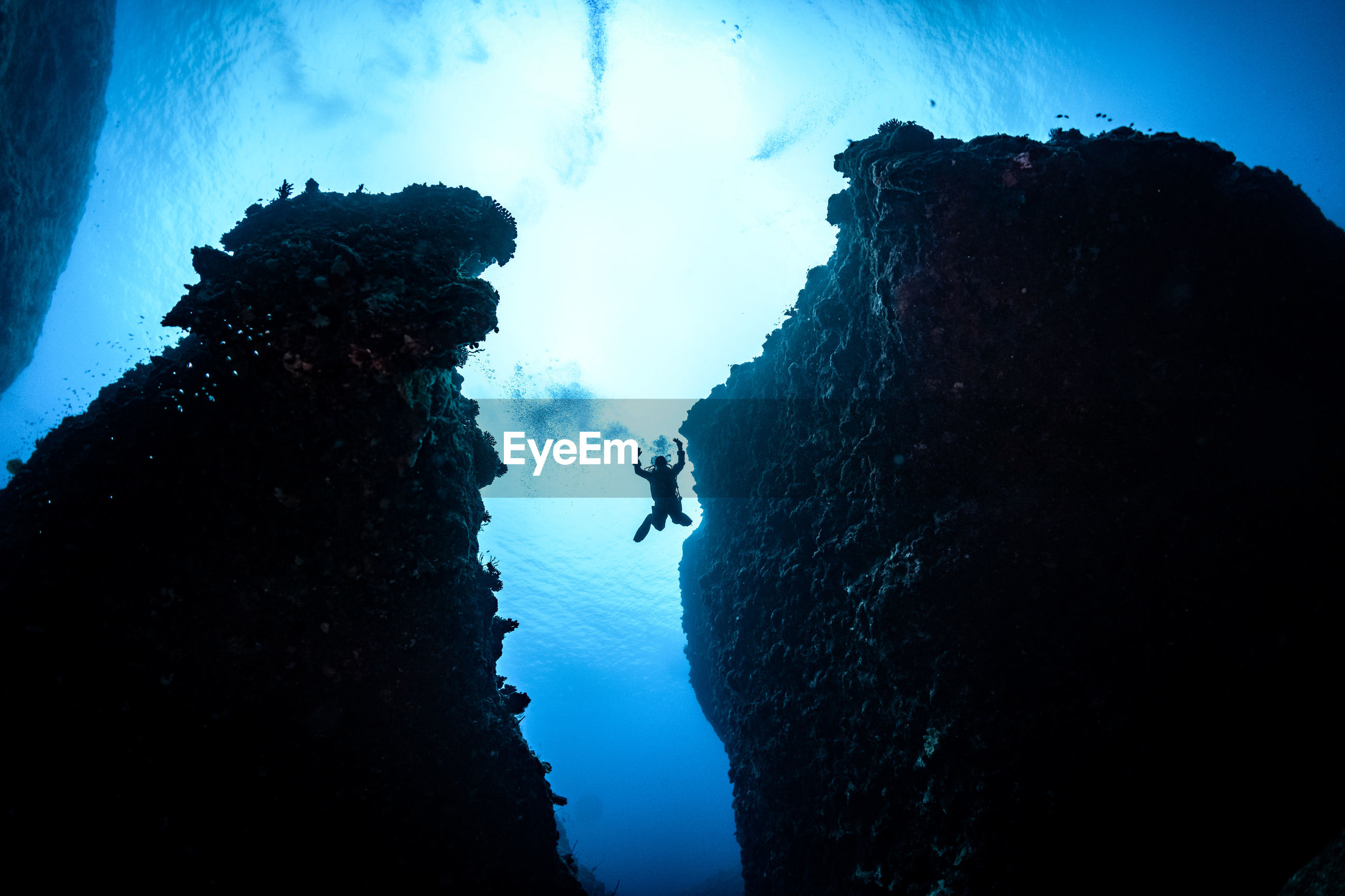 SILHOUETTE ROCK FORMATIONS IN SEA