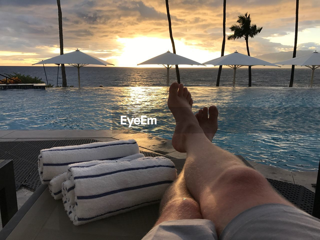 Low Section Of Man Relaxing At Poolside By Sea Against Cloudy Sky