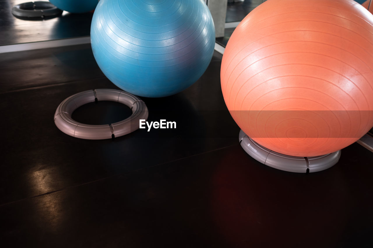 indoors, no people, still life, high angle view, table, close-up, shape, illuminated, lighting equipment, metal, design, geometric shape, circle, focus on foreground, orange color, blue, red, gym, equipment, sphere, silver colored