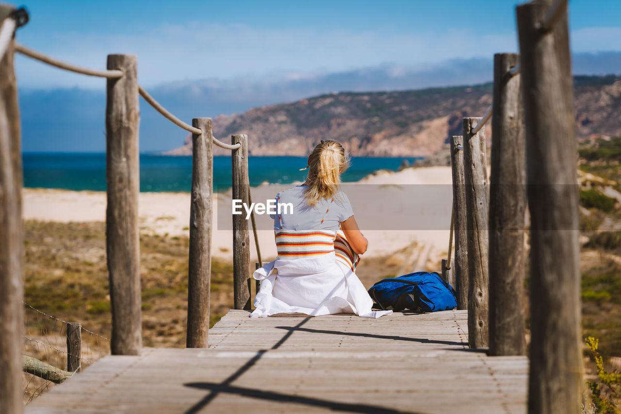 Rear view of woman sitting on boardwalk