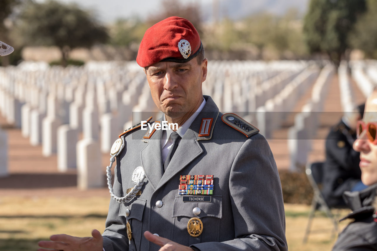 uniform, clothing, government, focus on foreground, military, portrait, men, military uniform, safety, real people, one person, day, protection, security, occupation, cap, front view, looking away, mature men, responsibility, officer, badge