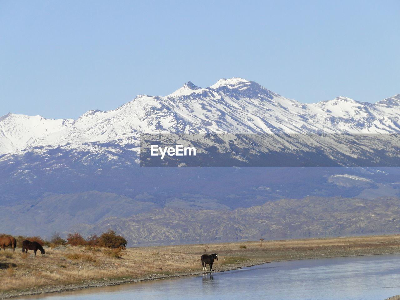 Calm Lake Against Snowed Mountain Range