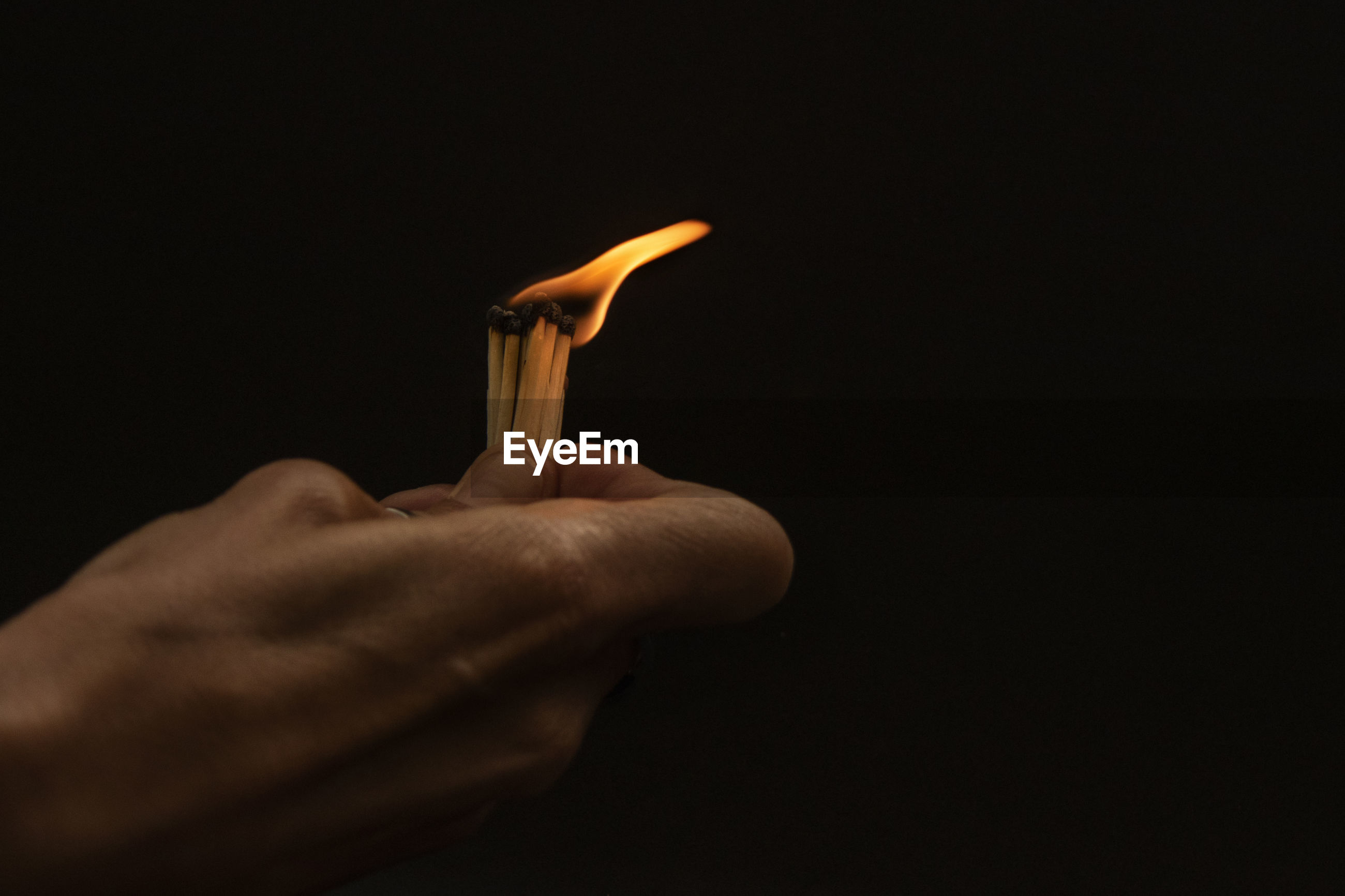 Close-up of hand holding matchsticks against black background