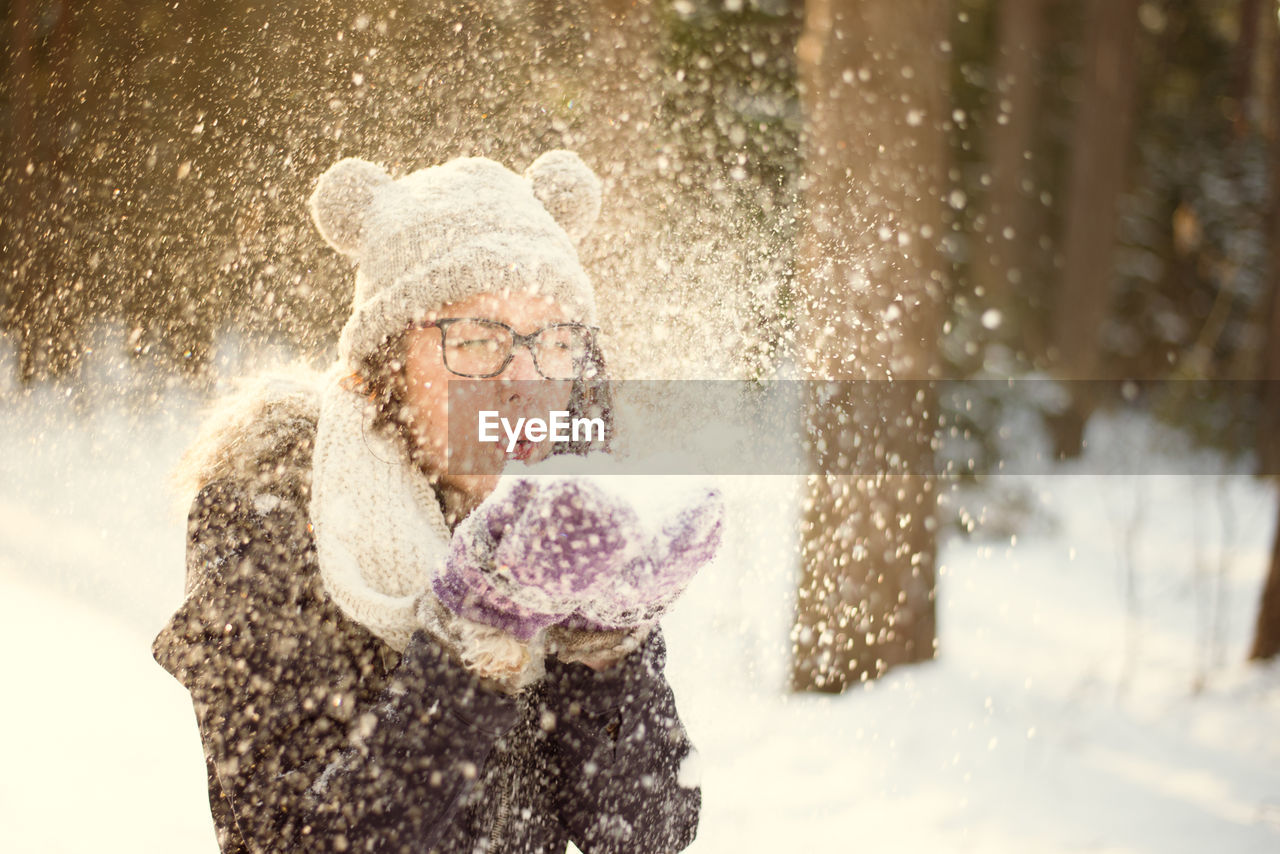 snow, winter, cold temperature, women, one person, fun, warm clothing, clothing, waist up, blowing, adult, motion, nature, enjoyment, snowing, emotion, females, scarf, positive emotion, outdoors