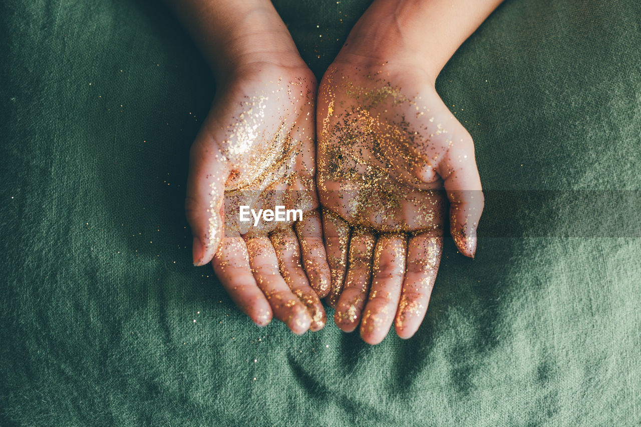 Close-Up Of Person Hand Covered In Glitter