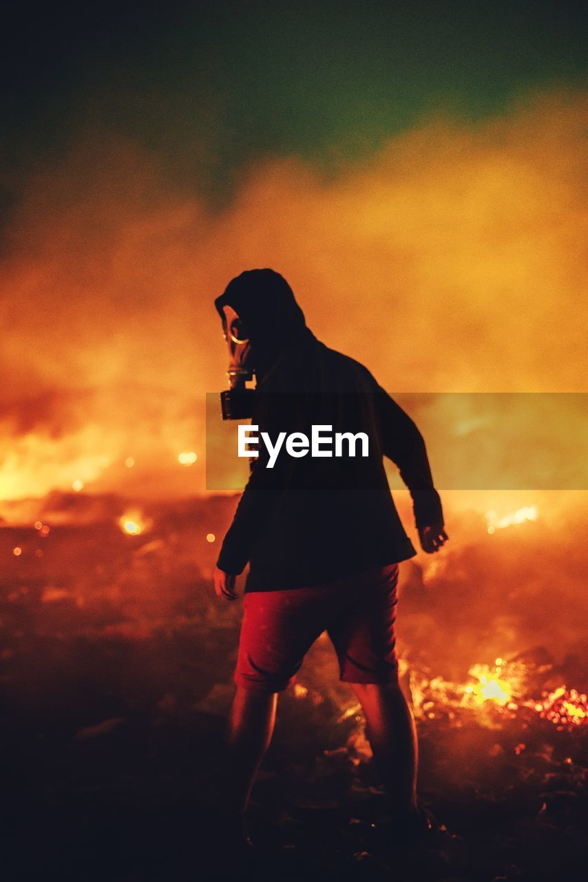 night, orange color, fire, fire - natural phenomenon, one person, flame, burning, full length, heat - temperature, nature, standing, smoke - physical structure, real people, sunset, young adult, men, warning sign, side view, motion