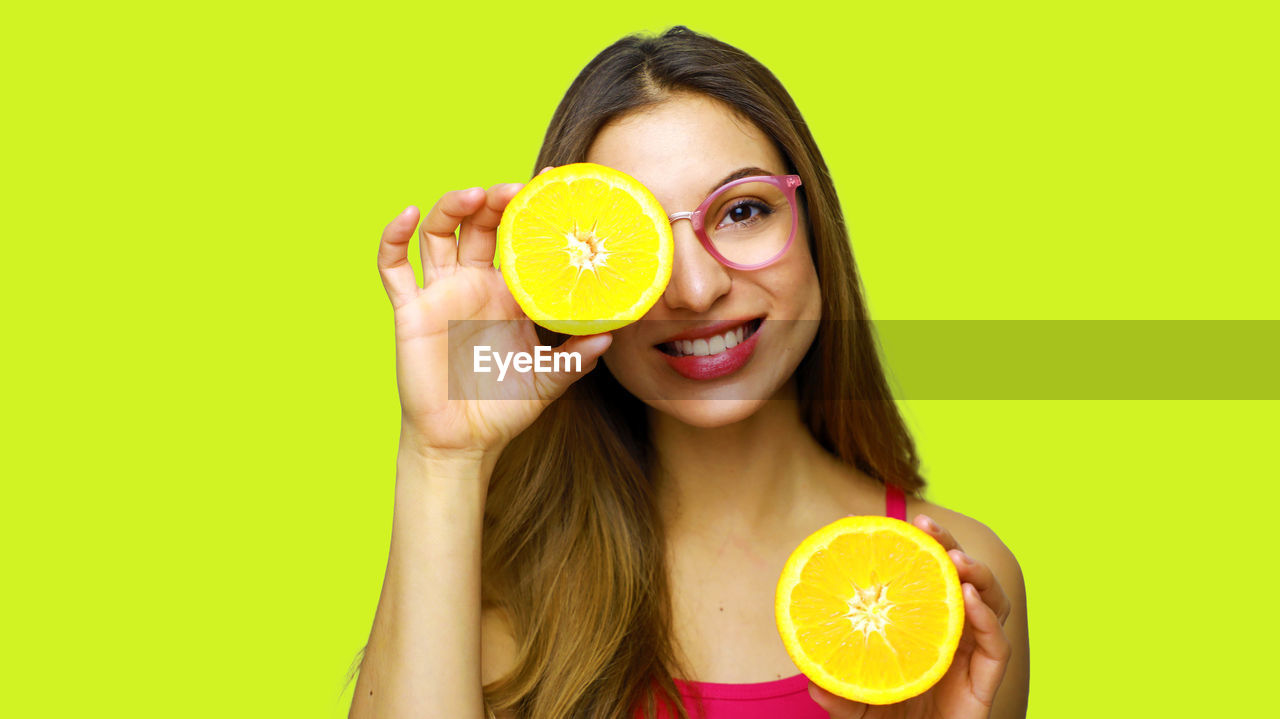 colored background, fruit, holding, citrus fruit, food and drink, studio shot, food, healthy eating, one person, portrait, women, yellow, smiling, wellbeing, young adult, adult, indoors, slice, looking at camera, lemon, beautiful woman, orange, hair, hairstyle, green background, yellow background, vitamin c