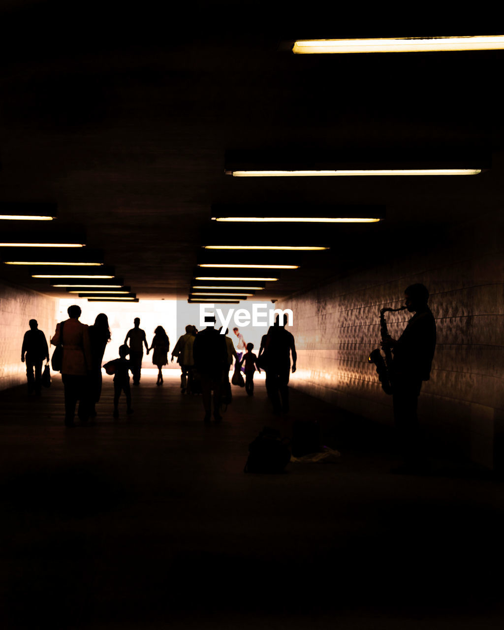 group of people, silhouette, real people, architecture, illuminated, indoors, men, subway, lighting equipment, public transportation, people, lifestyles, built structure, crowd, walking, women, standing, transportation, travel, flooring, ceiling, light, underpass