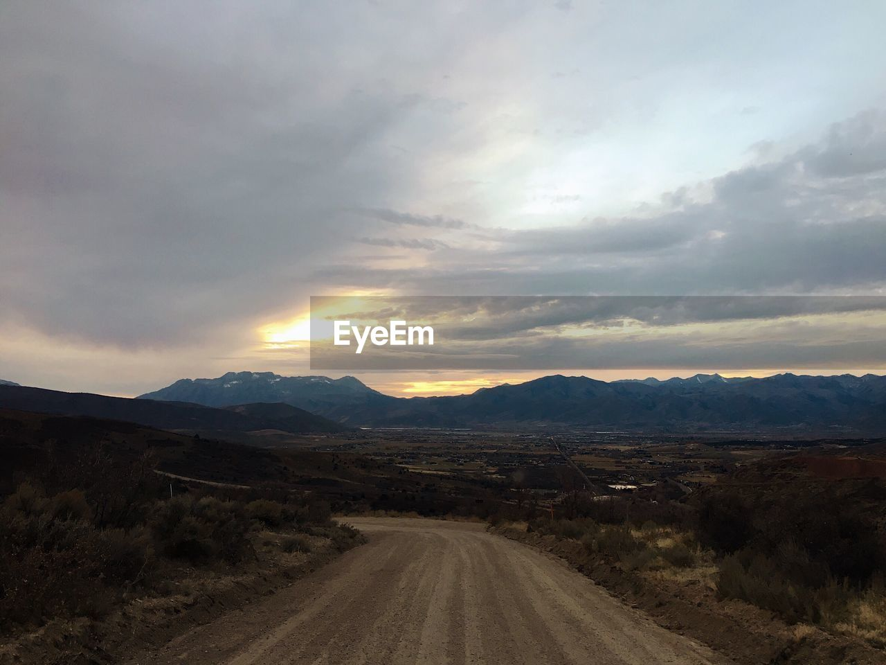 sky, cloud - sky, landscape, road, scenics - nature, environment, beauty in nature, mountain, the way forward, tranquility, direction, nature, transportation, tranquil scene, non-urban scene, no people, mountain range, diminishing perspective, dirt road, dirt, outdoors, long