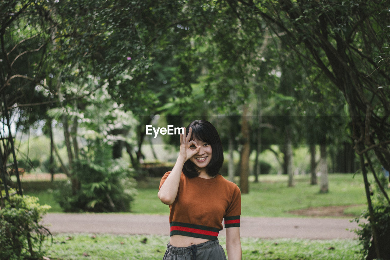 Portrait of smiling young woman gesturing while standing at park