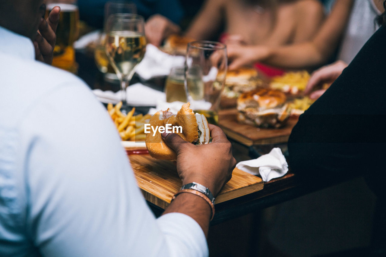 Midsection Of People Holding Food At Restaurant