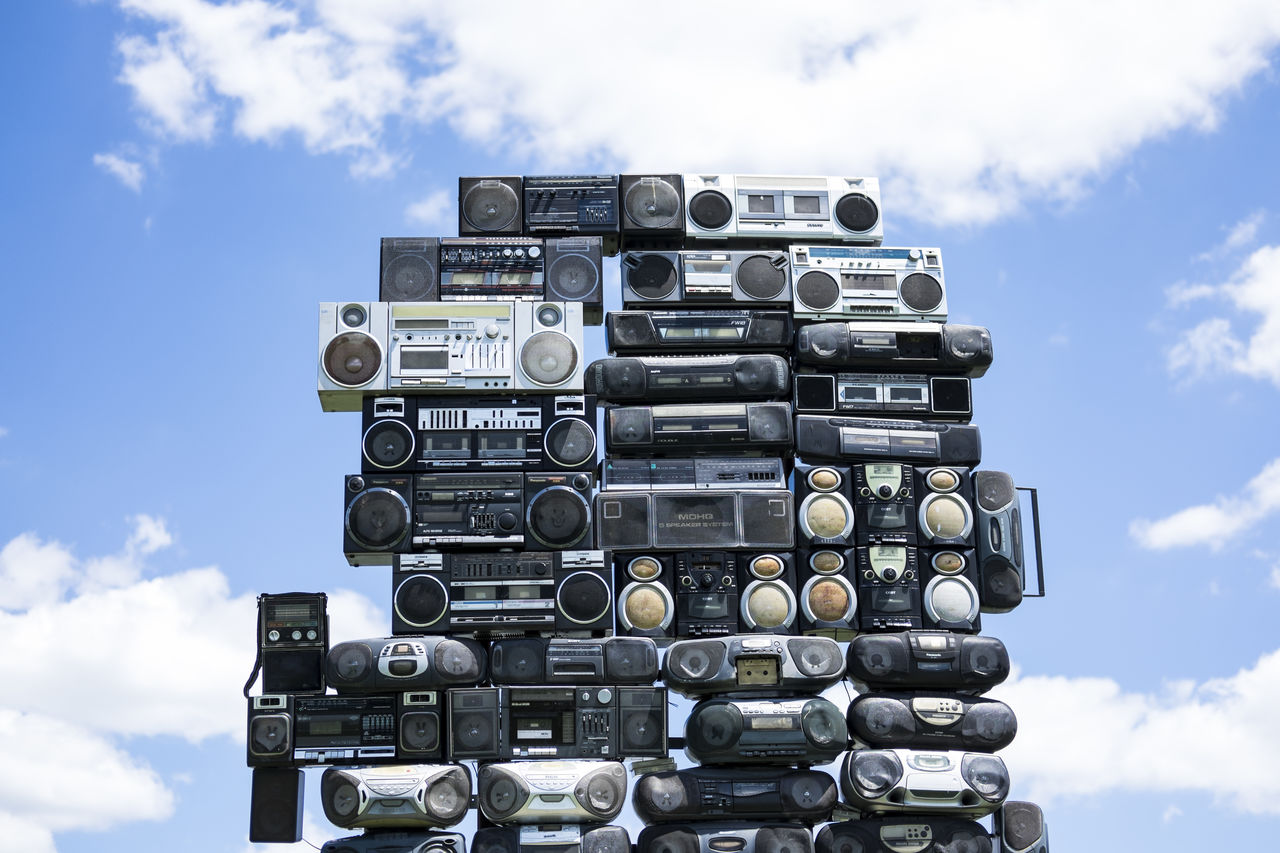 Stack of old-fashioned portable stereos against sky