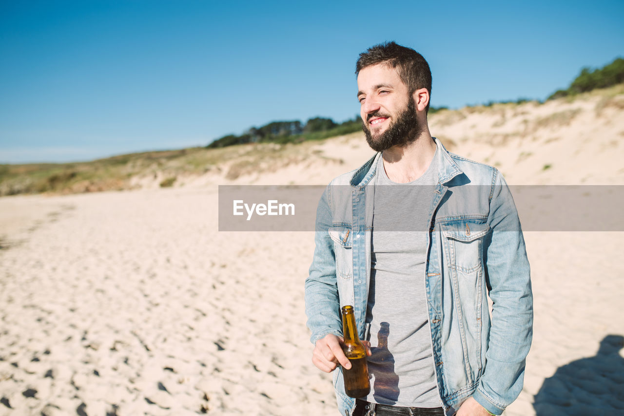 Young man holding alcoholic drink bottle while standing at beach during sunny day