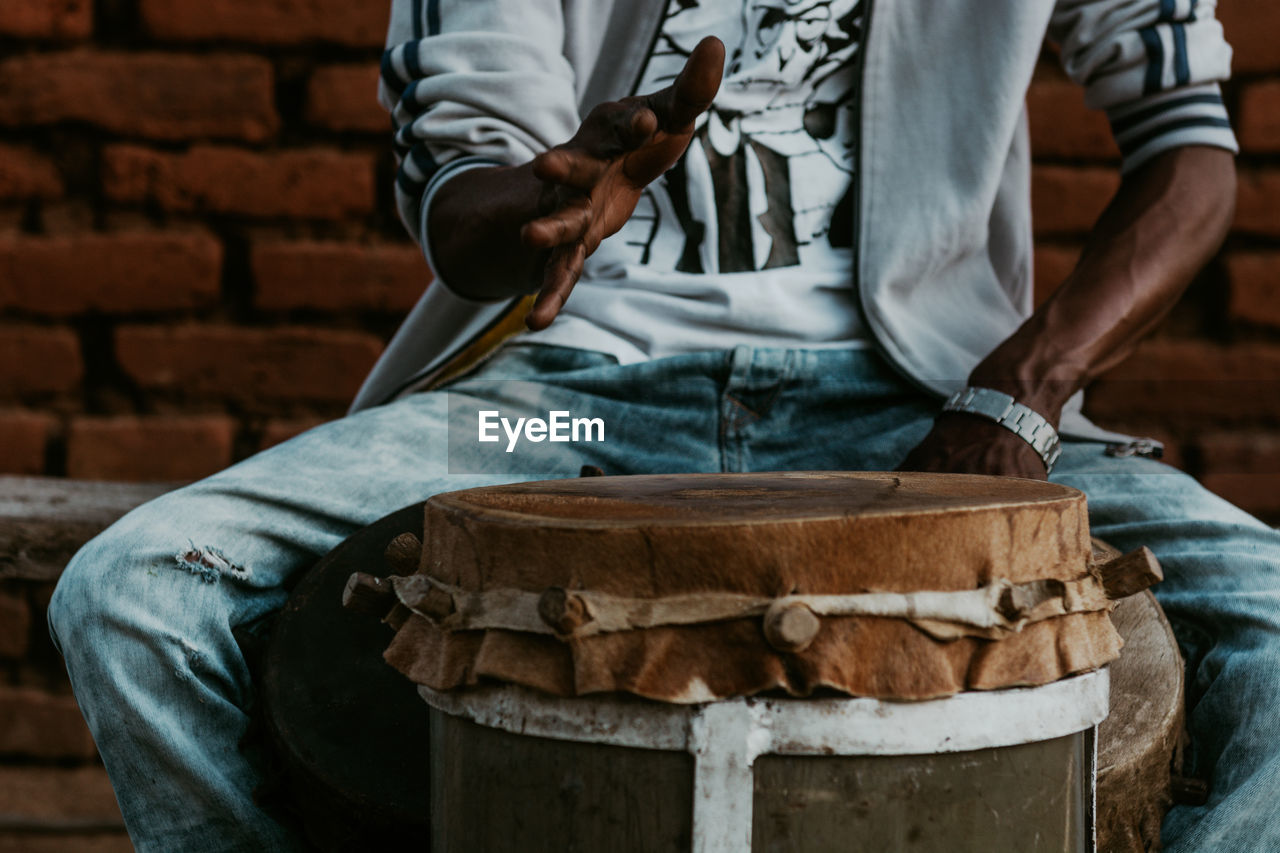 Midsection of man playing drums