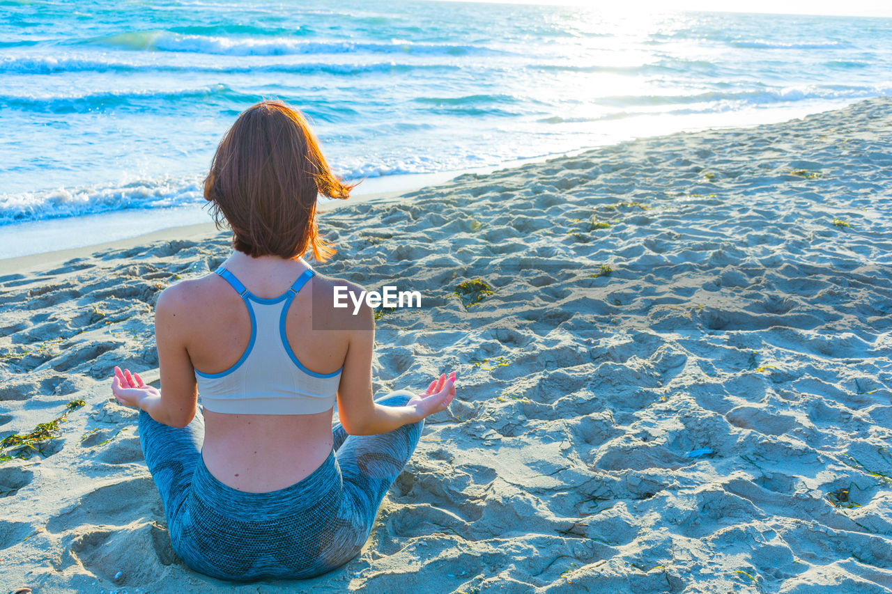 Rear view of woman meditating while sitting on sand at beach
