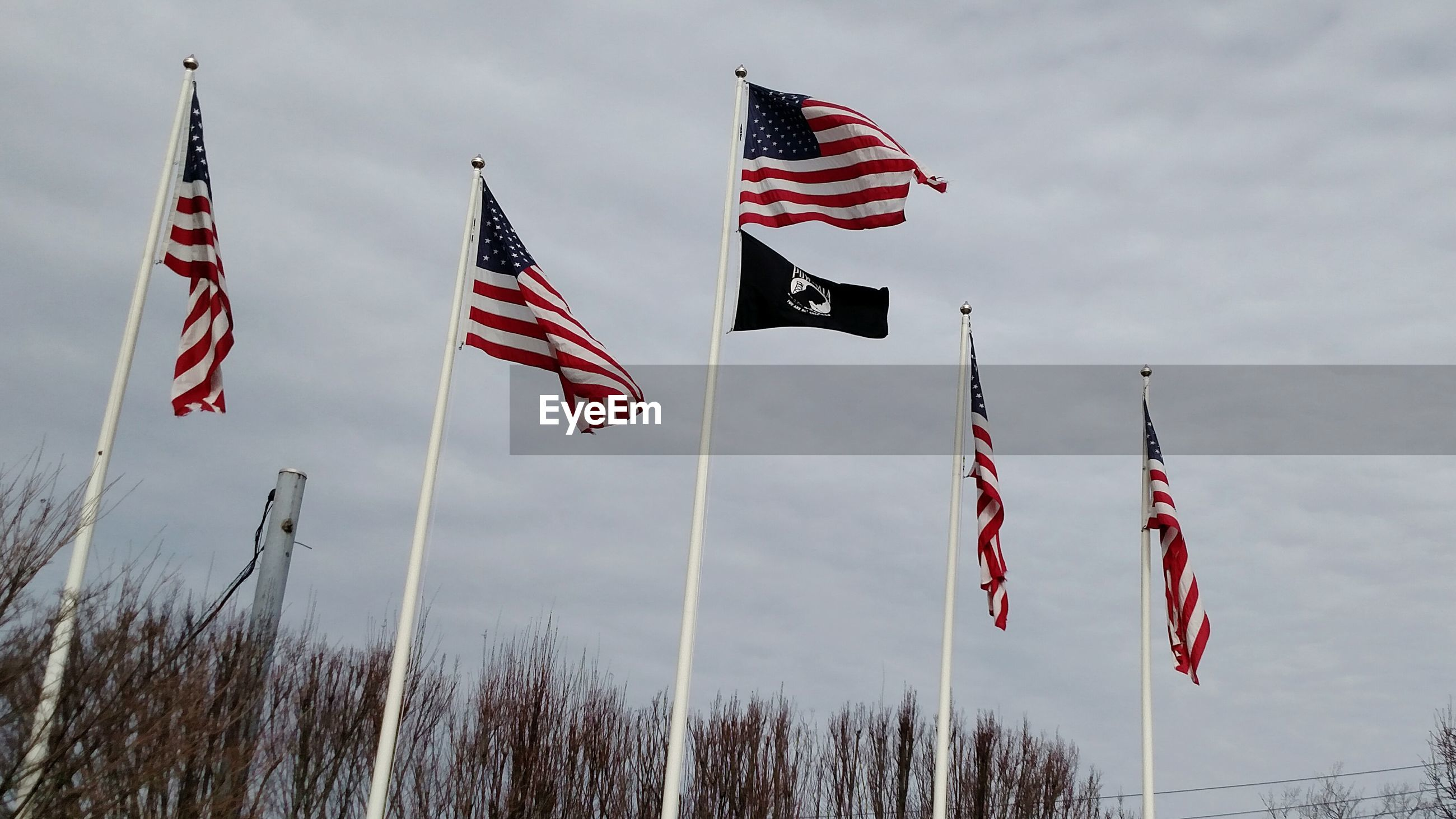 LOW ANGLE VIEW OF AMERICAN FLAG FLYING AGAINST SKY