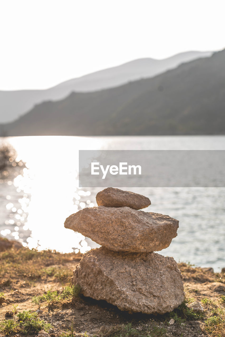 mountain, water, rock, tranquility, solid, stack, balance, beauty in nature, rock - object, nature, tranquil scene, scenics - nature, sky, zen-like, stone - object, focus on foreground, no people, day, lake, outdoors, pebble