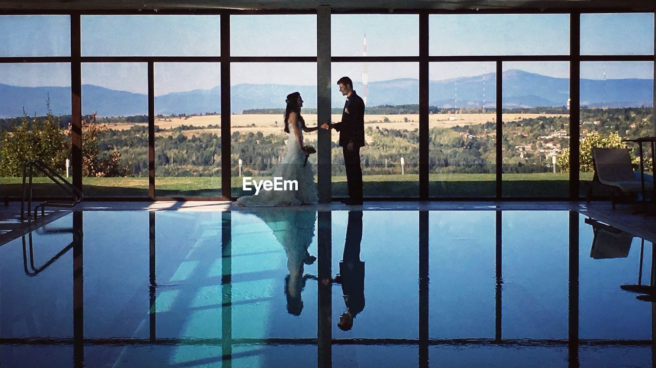 swimming pool, wedding, water, wedding dress, real people, bride, window, day, reflection, women, young women, well-dressed, indoors, young adult, standing, full length, sky, bridegroom, nature, people