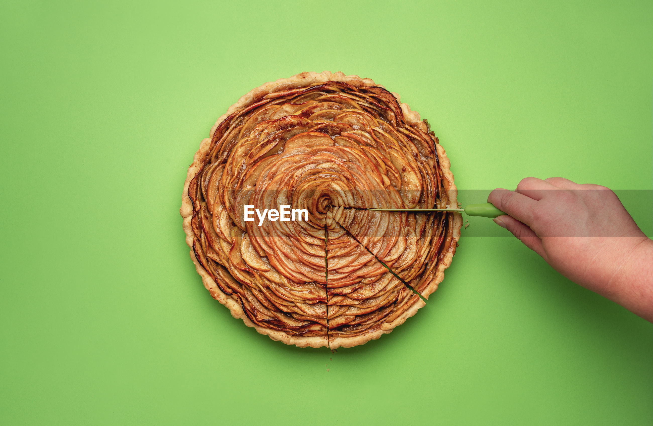 Cropped hand cutting apple pie on green background