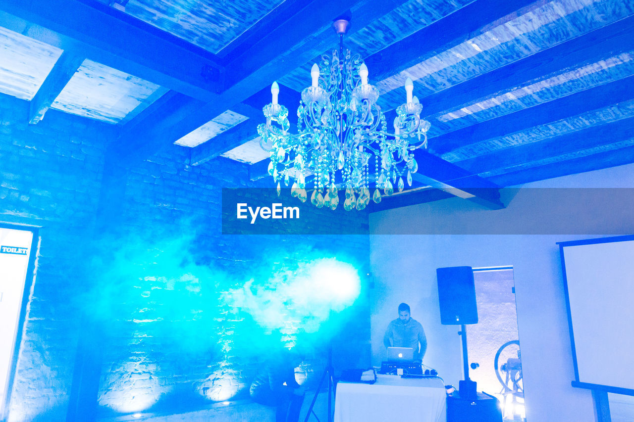 illuminated, indoors, lighting equipment, ceiling, decoration, no people, blue, low angle view, glowing, light, technology, chandelier, reflection, hanging, light - natural phenomenon, electric light, night, architecture, electric lamp, nightlife, light fixture