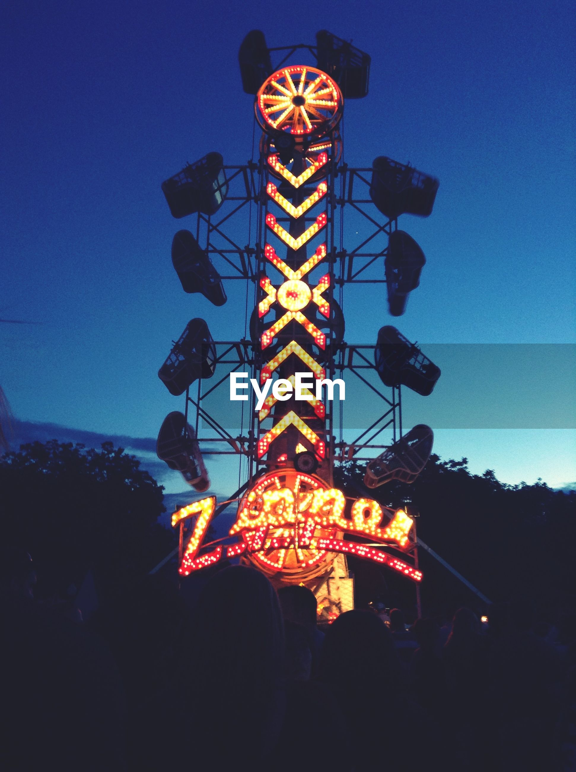 low angle view, illuminated, silhouette, blue, night, sky, clear sky, arts culture and entertainment, creativity, dusk, art, lighting equipment, leisure activity, art and craft, copy space, celebration, amusement park, multi colored, tree, outdoors
