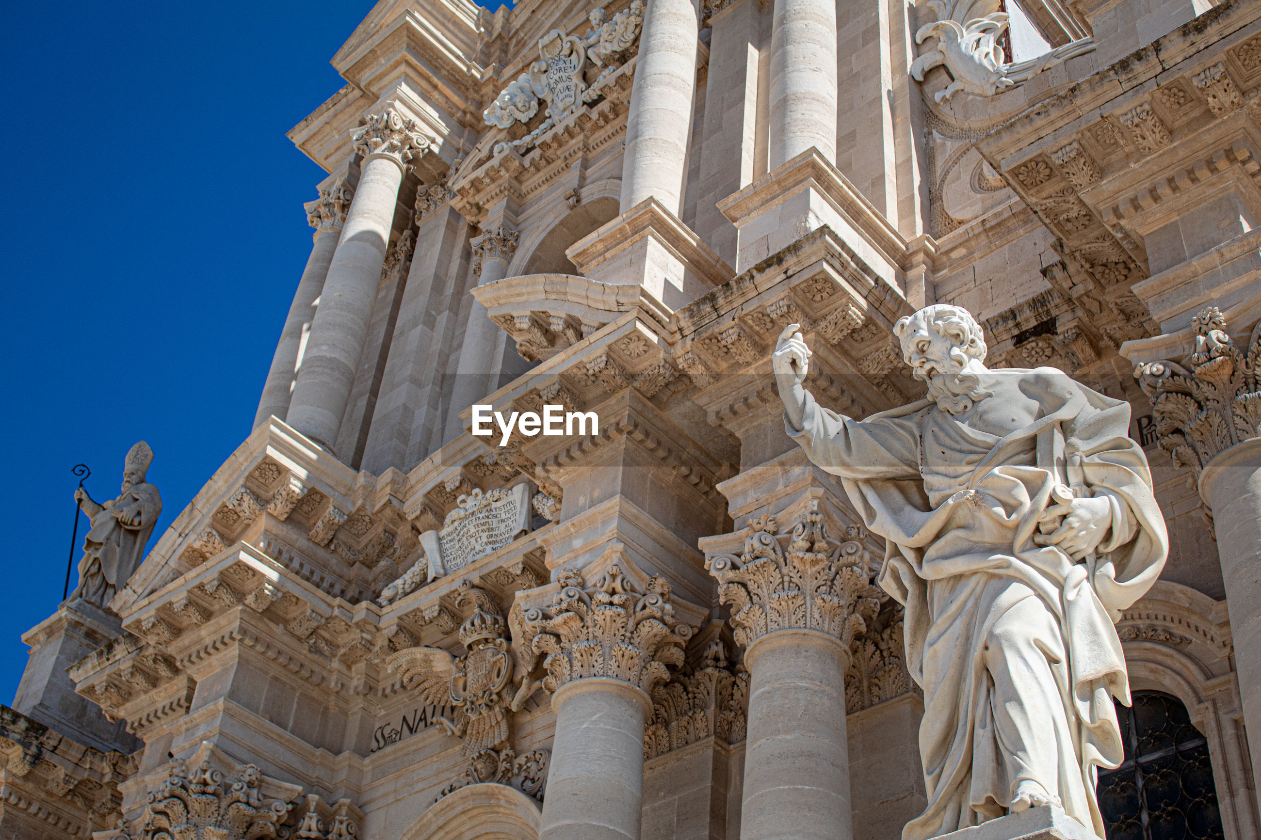 A statue of the ortigia cathedral with columns behind it, siracusa.