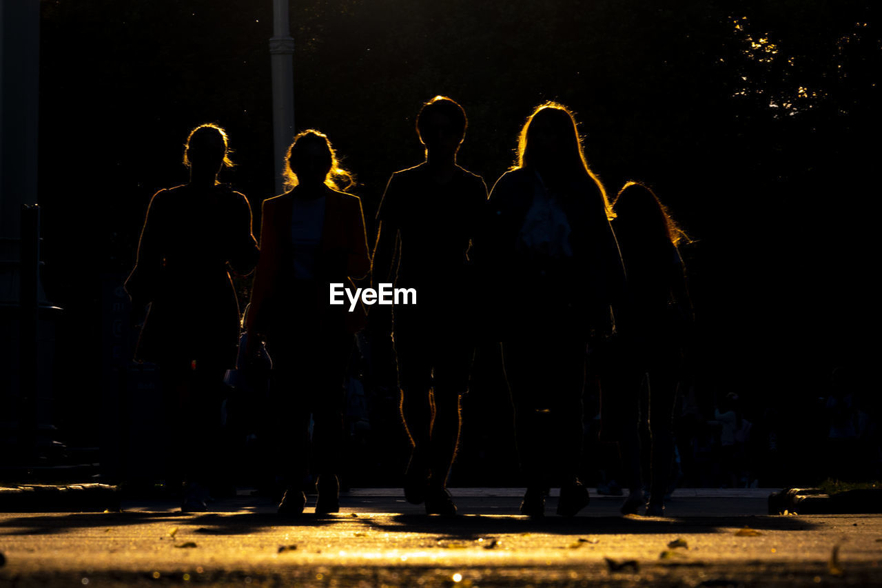 Silhouette people standing on street at night