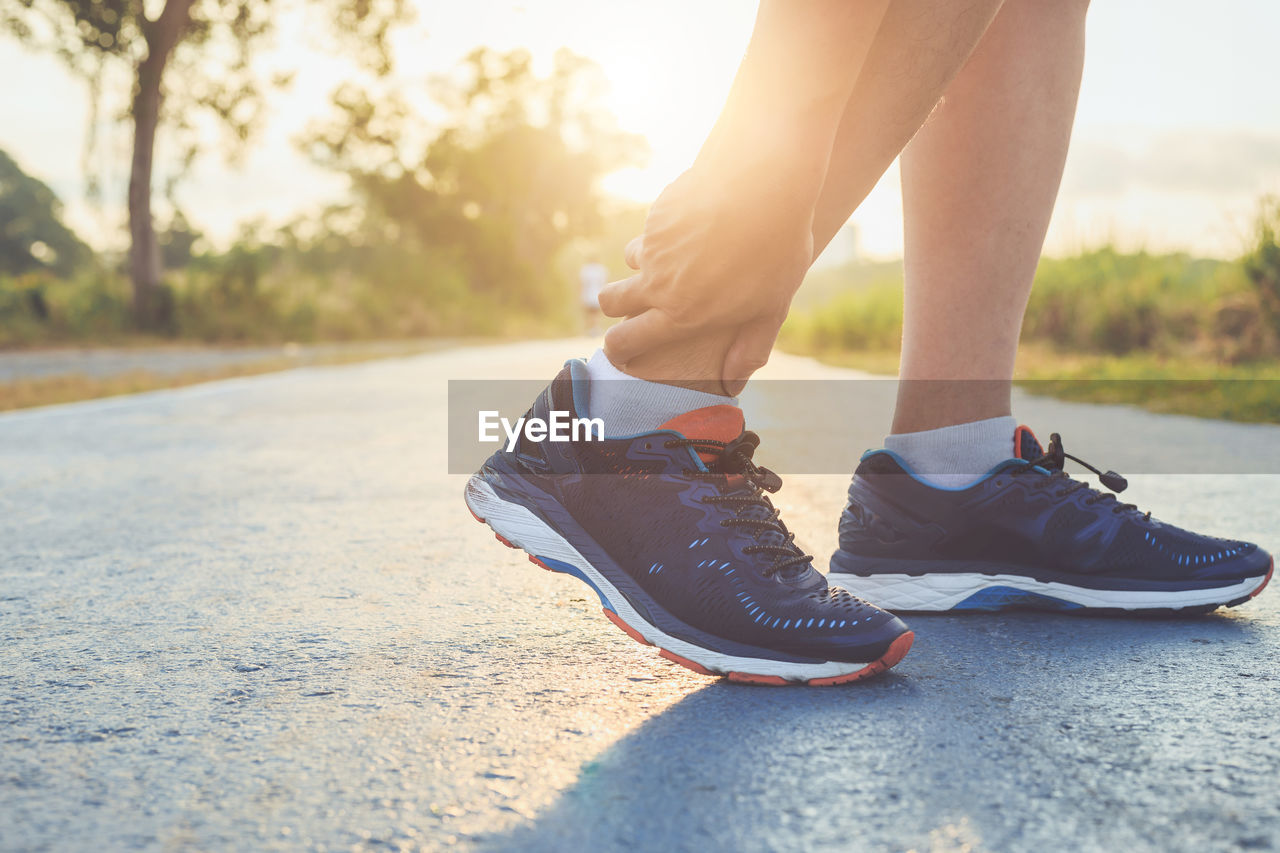 Low section of man in sports shoes on road